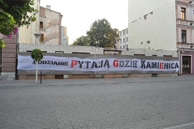 """We wrześniu 2012 r. na pozostałościach zburzonej kamienicy zawisł transparent: """"Łodzianie pytają gdzie kamienica""""."""