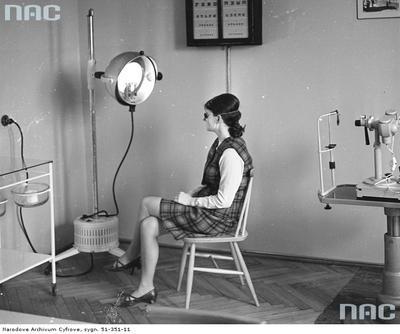 Młoda kobieta podczas naświetlania lampą kwarcową w gabinecie lekarskim w studenckiej przychodni.
