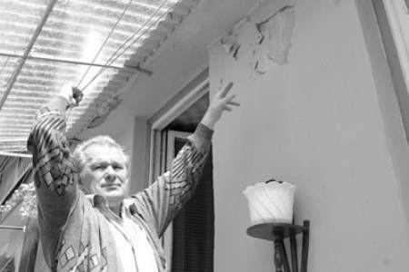 Aleksy Leks pokazuje nieocieplone, zniszczone ściany budynku.