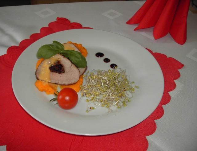 Polędwiczki wieprzowe z sosem holenderskim na marchewkowym puree (autor–Mariusz Walewski)  Składniki na 3 porcje:  •polędwiczka wieprzowa 1 szt. (ok. 300 g), •pomidory suszone w oliwie 100 g, •olej bazyliowo-czosnkowo-pomidorowy  20 g, •sos sojowy  15 g, •świeża bazylia (kilka listków), •olej do obsmażenia 10 g, •sól do smaku, •pieprz ziarnisty do smaku.  Puree z marchwi  •marchew 180 g,  •masło Bieluch 15 g, •mąka pszenna 6 g, •sól do smaku.   Sos holenderski •żółtka 40 g (2 szt.), •masło Bieluch 50 g, •ocet winny biały  22 g, •sól do smaku,  •pieprz biały do smaku.    Sposób przygotowania: 1.Polędwiczkę zamarynować w oleju smakowym, sosie sojowym, soli, pieprzu i posiekanej bazylii. Odstawić do lodówki na ok. 1 godzinę. 2.Marchewkę obrać, pokroić w części i ugotować z dodatkiem soli. Ugotowaną marchewkę odcedzić. 3.Masło rozpuścić w garnku, dodać marchewkę i oprószyć mąką, a następnie zmiksować i doprawić solą.  4.Pomidory odsączyć z zalewy i pokroić w paski.  5.Polędwiczkę wyjąć z marynaty. Nie rozcinając mięsa zrobić wąskim nożem otwór wzdłuż włókien. Nafaszerować polędwiczkę.  6.Na rozgrzaną patelnię wlać odrobinę oleju i obsmażyć mięso ze wszystkich stron. Następnie polędwiczkę przełożyć do naczynia żaroodpornego.  7.Piekarnik rozgrzać do 200 stopni i piec pod przykryciem przez 15 minut.  8.W garnku zagotować wodę. Do miski włożyć 2 żółtka, dodać sól, pieprz i ocet  winny. Ubijać  na parze. Masło rozpuścić i stopniowo dodawać do jaj, ciągle ubijając. Gdy sos zbieleje, przerwać ubijanie. 9.Polędwiczkę pokroić w plastry, ułożyć na puree z marchwi i polać sosem.   Wartość odżywcza 1 porcji potrawy:  Wartość energetyczna -  500 kcal,  białko: 12 g,  tłuszcz: 37 g,  węglowodany: 30 g