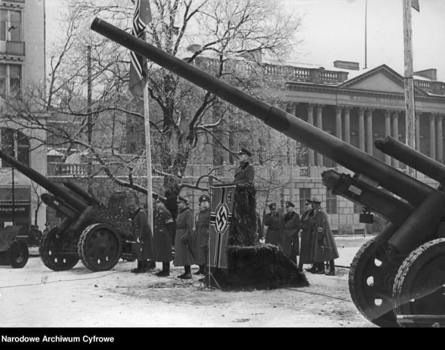 Poznań został zajęty przez Niemców 10 września 1939 roku. W czasie okupacji miasto wcielono do Niemiec jako stolicę Kraju Warty. W 1944 roku Poznań stał się twierdzą, a działania wojenne zakończyły się 23 lutego 1945 roku. W Narodowym Archiwum Cyfrowym znaleźliśmy zdjęcia miasta z lat 1939-1945. Zobacz galerię 20 okupacyjnych zdjęć Poznania.  Uroczystości na Wilhelmplatz w Poznaniu (obecnie pl. Wolności) związane z zaprzysiężeniem niemieckich oddziałów wojskowych złożonych z rekrutów pochodzących z Poznania. Przemawia komendant garnizonu. Widoczne armaty sK 18 kal. 100 mm. W tle widoczny gmach Biblioteki Raczyńskich.  Przejdź dalej --->