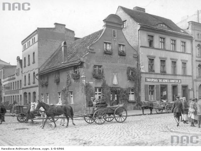 Hotel Modry Fartuch - widok zewnętrzny. Przed hotelem na ulicy widoczne wozy  Data: 1925-10  Hotel Modry Fartuch w Toruniu