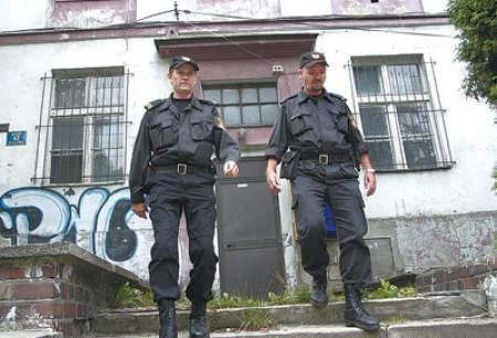 Starszy strażnik Marek Hejczyk i inspektor Tomasz Staniec podczas obchodu opustoszałego budynku.