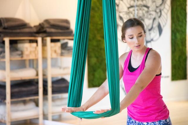 Aerial joga, nazywana treningiem w powietrzu lub jogą z chustą/hamakiem, to możliwość uzyskania świadomego panowania nad swoim ciałem w nieco innej formie. Dzięki grawitacji, wszystkie ćwiczenia wykonuje się z niezwykłą łatwością i lekkością, o czym przekonaliśmy się na własnej skórze. O jodze w powietrzu nie tylko rozmawiamy, ale też praktykujemy, z Martyną Czyżewską - instruktorką jogi - która stworzyła oazę w centrum biznesowego Mokotowa i dzieli się swoim uwielbieniem do ćwiczeń na hamaku. Szczegóły i wideo w artykule poniżej.