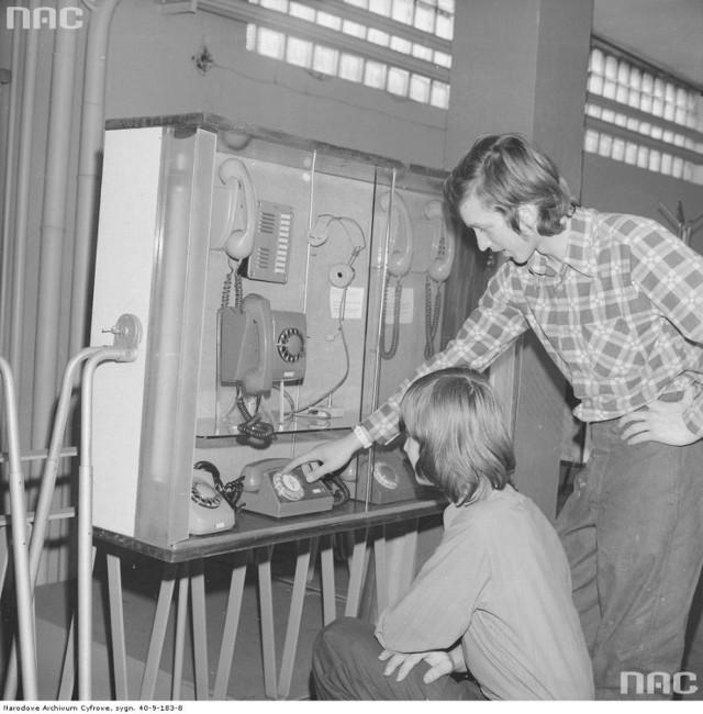 Robotnicy przy nowych aparatach telefonicznych Radomskiej Wytwórni Telefonów. Na dole od lewej telefony: Jaskier, Storczyk, Aster. Wyżej wiszący aparat Irys. Rok 1976