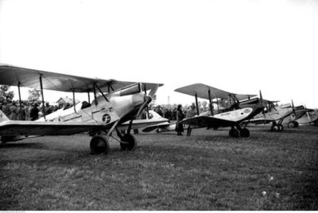 Uczestnicy uroczystości oglądają samoloty stojące na lotnisku. Od lewej widoczny samolot PZL.5 ,dalej De Havilland DH.60 Moth