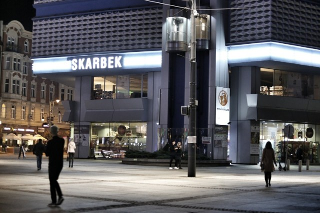 """Neon na Skarbku tworzą trzy  duże napisy """"Skarbek"""" połączone potrójną świetlną kreską"""