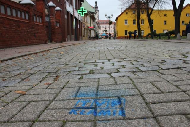 """Napisy o treści """"TVP Kłamie"""" oraz """"Dość propagrandy PiS"""" możemy znaleźć na chodnikach m.in. przed wejściem do poczty, cmentarza oraz księgarni w Grodkowie."""