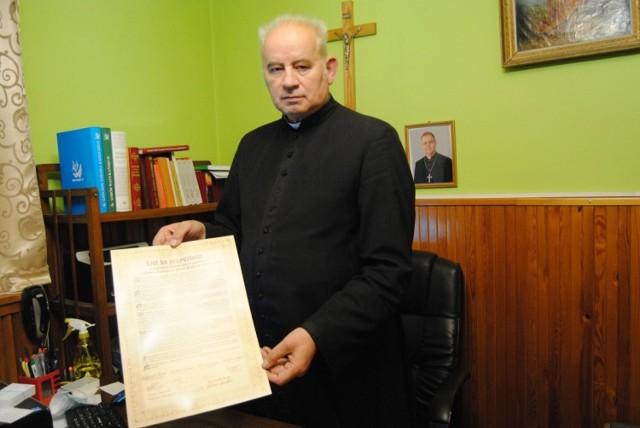 """Ksiądz prałat Zygmunt Pawlik prezentuje """"List ku przyszłości"""", który został umieszczony w pozłacanej kuli wieńczącej kościelną wieżę."""