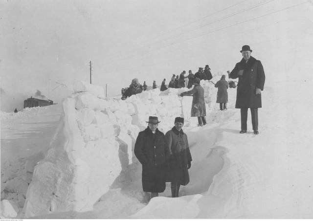 """Takich zim w Polsce nie było już od lat. Narodowe Archiwum Cyfrowe przygotowało fotografie ze swoich zbiorów, na których widać, jak Polska walczyła z białym puchem przed laty.  Zasypane drogi, tory, chodniki. Przed laty śniegu w Polsce było tak dużo, że z miast trzeba go było wywozić ciężarówkami. Po zasypanych śniegiem torach musiały jeździć pługi śnieżne. Pługi jeździły też po drogach. Białego puchu było czasem tak dużo, że ciężkie pługi nie mogły się przez niego przebić.  Zobacz na zdjęciach jak wyglądała zima przed laty.  Zobacz też wideo: """"Miasto wygląda pięknie"""". Mieszkańcy Warszawy zadowoleni z opadów śniegu   Przeczytaj też:  Zima w Lubuskiem. Śnieg spadł w wielu miejscowościach. Zobaczcie zdjęcia"""