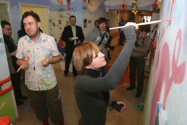Ania Wyszkoni maluje korytarz na oddziale dziecięcym