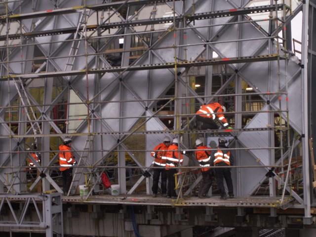 Trwa montaż szyb na łukowo wygiętej części konstrukcji przyszłego dworca kolejowego.