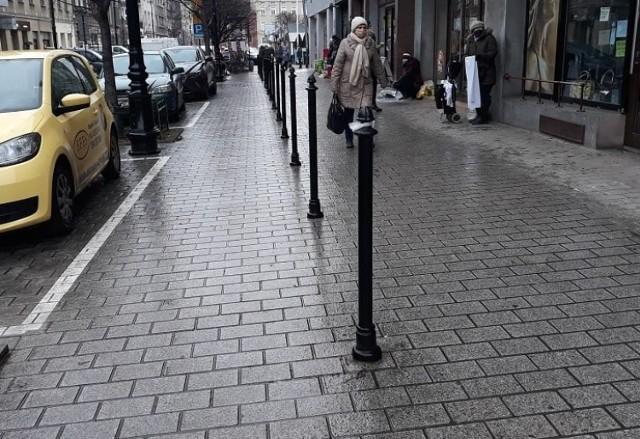 Słupki na chodniku na ul. Rynek Kleparski. Wyznaczają one ukośne miejsca parkingowe