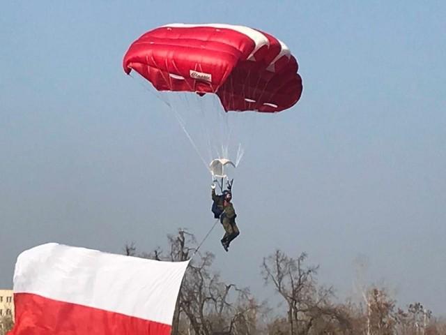 Policjant w roli spadochroniarza z biało-czerwoną flagą nad Gnieznem