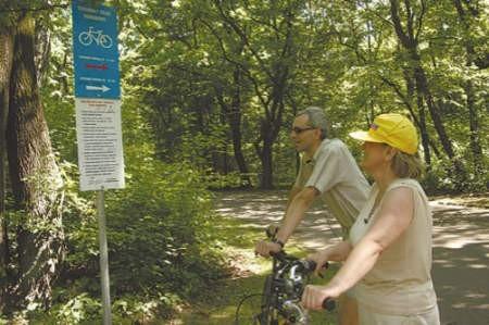Mariola Ratajczak i Grzegorz Siodłak przy tablicy z regulaminem ścieżki rowerowej.