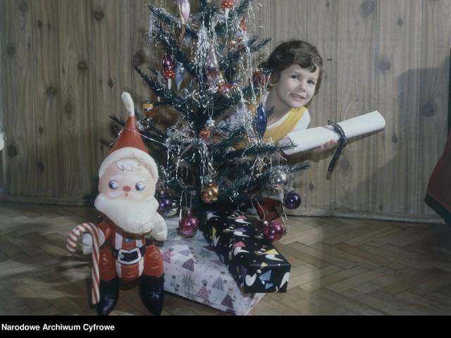 Dziecko pod choinką z rulonem papieru w ręku. Na pierwszym planie widać nadmuchiwanego Świętego Mikołaja i zapakowane prezenty.  1976 r.