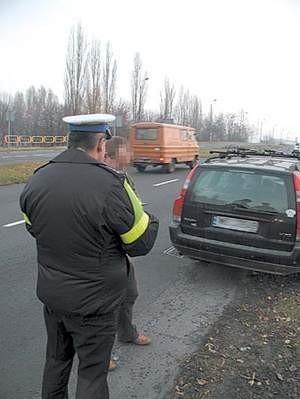 Nadkomisarz Krzysztof Kiercz tłumaczy zatrzymanemu kierowcy, na czym polegało jego przewinienie.