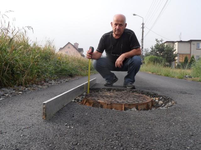 Pan Roman mierzył dziury  między studzienkami a nawierzchnią ulicy
