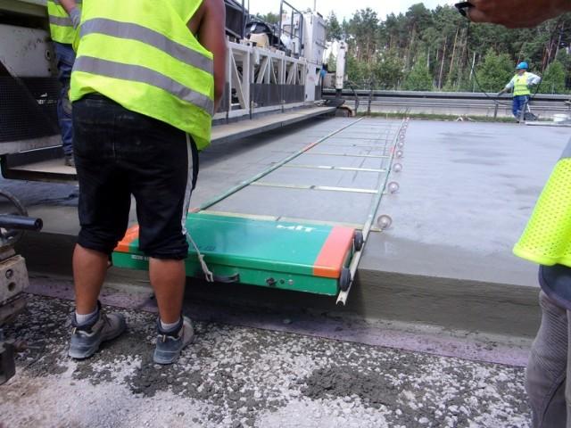 """Trwają prace przy budowie A18. Na odcinku między węzłami Żary Zachód i Iłowa, na modernizowanej jezdni południowej został ułożony testowy odcinek nawierzchni betonowej o długości 500 m.   Nawierzchnia betonowa bardziej wymagająca  - Odcinek próbny układa się w celu sprawdzenia, czy zastosowane materiały, technologia i jakość wykonanych prac gwarantują otrzymanie nawierzchni o pożądanych parametrach. Jest to bardzo istotne, bo reżim układania nawierzchni betonowej jest znacznie bardziej rygorystyczny niż przy nawierzchni bitumicznej (nazywanej potocznie asfaltową) – wyjaśniają specjaliści z zielonogórskiego oddziału Generalnej Dyrekcji Dróg Krajowych i Autostrad. - Jeśli badania potwierdzą odpowiednią jakość wykonanej nawierzchni, wówczas wykonawca dostanie zielone światło do jej ułożenia na pozostałym odcinku modernizowanej drogi.  Jeszcze przed ułożeniem mieszanka betonowa badana jest pod kątem konsystencji, zawartości powietrza i gęstości. Natomiast po 28 dniach od ułożenia sprawdzana jest m.in. wytrzymałość na ściskanie, zginanie i rozciąganie, a także mrozoodporność. Nawierzchnia badana jest również pod kątem takich parametrów jak równość podłużna i poprzeczna czy współczynnik tarcia.  Lubuski odcinek A18 będzie gotowy w przyszłym roku  Budowany odcinek autostrady ma długość 22 km i zaczyna się w okolicach węzła Żary Zachód w stronę Wrocławia, a kończy ok. 4 km przed węzłem Iłowa. Jest jednym z czterech odcinków, na które podzielona została inwestycja mająca na celu przebudowę jezdni południowej drogi krajowej nr 18 od Olszyny do węzła w Golnicach (71 km). Jest także odcinkiem o największym stopniu zaawansowania prac. Ma być gotowy w II połowie 2022 roku.   Zobacz, jak wygląda układanie betonowej nawierzchni:    Wideo: Budowa A18 1 Lubuskiem  materiał z 16.06.2021  Czytaj także: """"Najdłuższe schody Europy"""" w przebudowie. Zobacz, jak przebiegają prace dotyczące autostrady A18"""
