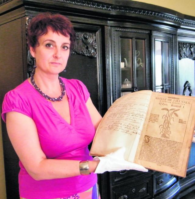 Monika Sitek, pracownica muzeum, prezentuje unikatowe dzieło Szymona Syreniusza
