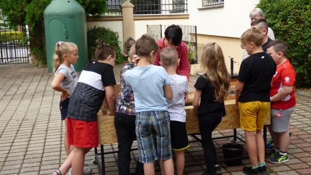 Dzieci podczas zajęć z instruktorką Magdaleną Birut na podwórku Muzeum Miejskiego w Nowej Soli.