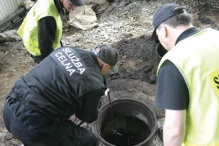 Celnicy nad włazem do zakopanej cysterny.