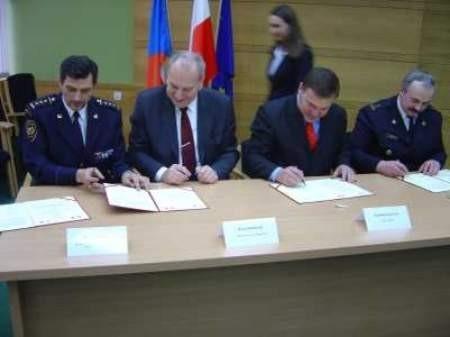 Zdenek Nytra, Evžen Tošenovský, Zygmunt Łukaszczyk oraz Marek Rączka podpisują umowę.