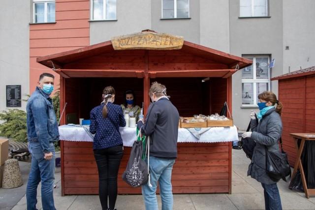W niedzielę (26 kwietnia) na plac przed Drukarnię przy ul. Gdańskiej 8, ku uczesze wielu miłośników ekojarmarku, powrócili niemal wszyscy frymarkowi wystawcy, oferujący swe regionalne produkty. Jarmark odbył się przy zachowaniu zasad ostrożności. Kolejny Frymark  w niedzielę, 3 maja.   Jak wyjaśniają organizatorzy, po przeanalizowaniu sytuacji i wprowadzeniu zasad ostrożności, zdecydowano się przywrócić Frymark bydgoski. Przypomnijmy, jarmark w związku z sytuacją epidemiologiczną od połowy marca został zawieszony, choć oficjalnie władze nie zamknęły targowisk. Frymarkowi wystawcy od ponad miesiąca oferowali jednak swe produkty głównie przez telefon lub sklep internetowy z możliwością dowozu m.in. do Bydgoszczy, a nawet pod drzwi klientów. Od ostatniej niedzieli kwietnia produkty znów można kupi na miejscu – na jarmarku przy Gdańskiej 8, który odbywa się pod pewnymi rygorami zachowania bezpieczeństwa.   Frymark bydgoski jak zawsze obywa się w niedziele w godz. 10-14, ale wyłącznie na wolnej przestrzeni, czyli na placu przed Drukarnią, na który wpuszczana jest ograniczona liczba klientów – w niedzielę, 26 kwietnia, czuwał nad tym pan Bartek.  Klienci proszeni są oczywiście o noszenie maseczek, trzymanie dystansu (rekomendowana odległość 2 m),  dezynfekowanie rąk.    Wystawcy niemal w komplecie pojawili się na pierwszym po przerwie jarmarku. Co ważne, podczas Frymarku bydgoskiego można zrobić zakupy, ale można też odebrać produkty zamówione wcześniej online poprzez www.sklep.frymarkbydgoski.pl, który ma już w ofercie przeszło 540 produktów. Klientom, którzy nie chcą przychodzić na stacjonarny Frymark przy Gdańskiej 8, zamówienia są dostarczane bezpośrednio pod dom.   Kolejny Frymark bydgoski jest planowany w niedzielę, 3 maja. Kto chce złożyć zamówienia online, powinien zrobić to do południa 30 kwietnia, dowóz paczek z produktami będzie po niedzielnym jarmarku stacjonarnym.