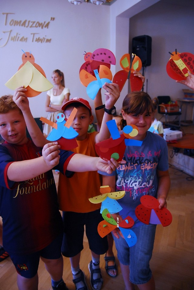 Uczestnicy wakacji w bibliotece pokazują prace plastyczne wykonane podczas piątkowych warsztatów