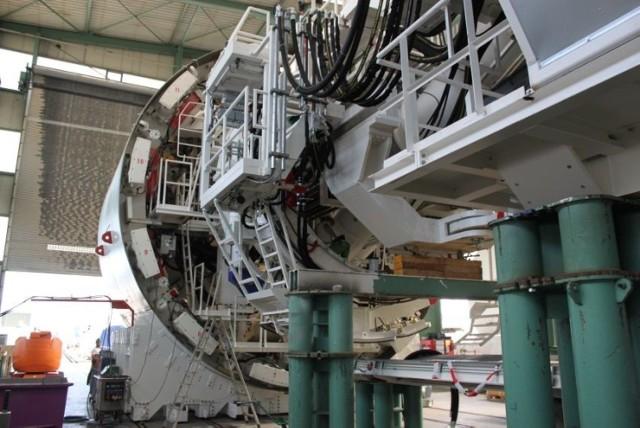 Maszyna pracuje w niezwykle nowatorskiej technologii EPB (Earth Pressure Balance). Z grubsza rzecz biorąc chodzi o to, że drążony przez tarczę grunt nie jest od razu usuwany na powierzchnię, ale gromadzony w komorze wydobywczej za tarczą. Jest tam wykorzystywany do równoważenia nacisku, jaki na tarczę wywiera czoło wykopu. Nadmiar urobku jest zabierany przez przenośnik ślimakowy i przenoszony na zewnątrz. Czujniki cały kontrolują równowagę ciśnienia ziemi przed i za tarczą. Taka technologia zapobiega osiadaniu gruntu i przedostawaniu się wody do tunelu, a także zapewnia maksimum bezpieczeństwa dla obiektów na powierzchni, co ma niebagatelne znaczenie w przypadku Łodzi, gdzie kamienice często wznoszono na wątłych fundamentach.  Maszyna potrafi się również dostosować do pracy z różny-mi rodzajami gruntu. Przez wstrzykiwanie bentonitu, wo-dy lub piany może zmieniać parametry urobku. Po wydrążeniu określonego odcinka tunelu jeden z modułów maszyny, tzw. erektor, zaczyna układać obudowę tunelu. Prefabrykowane, zbrojone betonowe panele są układane pierścieniowo i uszczelniane specjalną mieszanką. Następnie tarcza drążąca, popychana przez hydrauliczne siłowniki, zaczyna kolejny odcinek, obracając się z prędkością trzech obrotów na minutę. W ten sposób TBM może wydrążyć dziennie około 10 metrów tunelu.