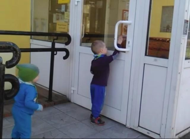 Dziecko próbuje dostać się do sklepu w niedzielę