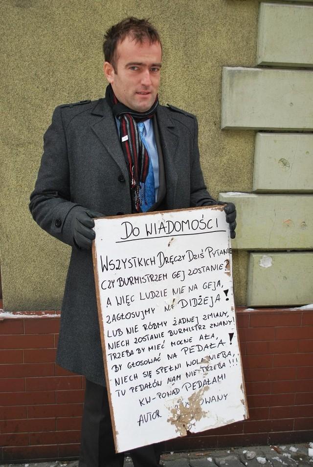 Dariusz Tuszyński pokazuje tablice z obraźliwym wierszem