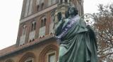 """Toruń. Kopernik jako słup ogłoszeniowy? Jest przebierany, """"przystrajany"""" lub traktowany jak miejsce na plakaty. Czy tak powinno być?"""