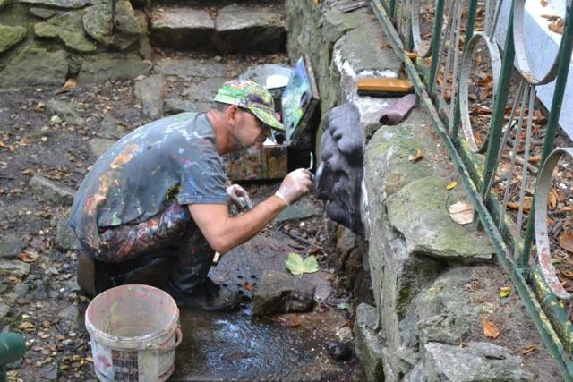 Adam Plackowski podczas renowacji lwa przy źródełku