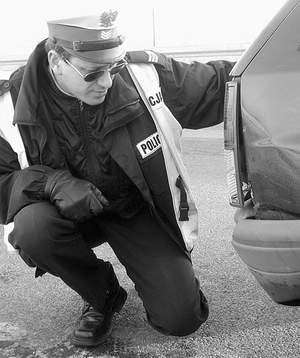 Sierżant sztabowy Andrzej Lewicki podczas oględzin samochodu na miejscu kolizji. Fot: SYLWESTER  WITKOWSKI