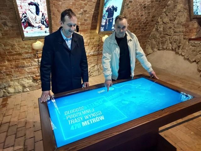 od lewej - Wojciech  Dumin, dyrektor Sandomierskiego Centrum Kultury i Grzegorz Bańkowski pomysłodawca wystawy multimedialnej nad tablicą multimedialną, na której  z lotu ptaka można zobaczyć, pod którymi kamienicami i ulicami na starówce przebiega podziemna trasa turystyczna.