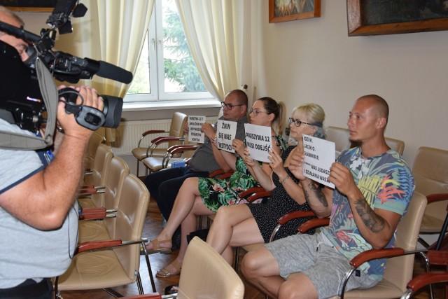 Grupa mieszkańców prezentująca na kartkach hasła, co miało miejsce na sesji nadzwyczajnej Rady Miejskiej w Żninie 26 lipca 2021 r. W porządku obrad był jeden punkt dotyczący obniżki pensji burmistrza. Więcej w tekście niżej.