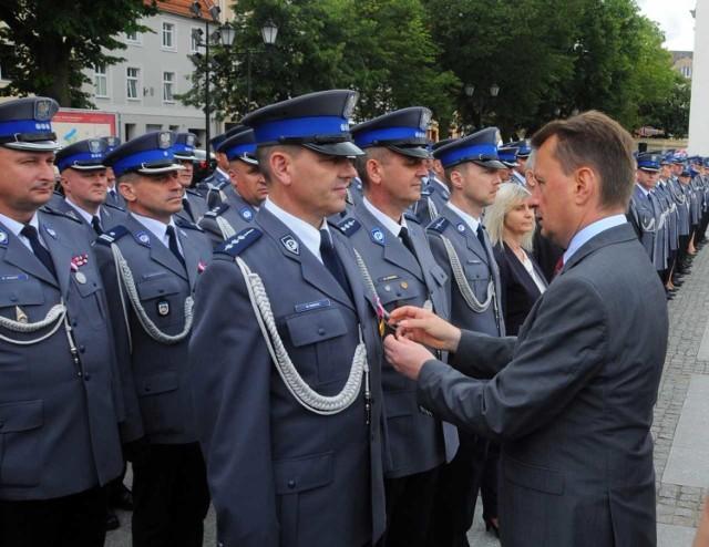 """W piątek - po długim i gruntownym remoncie - do użytku oddana została siedziba Komendy Powiatowej Policji w  Chełmnie. Jednostce nadany został także sztandar. Na te uroczystość, którą połączono z obchodami Wojewódzkiego Święta Policji, przyjechał Mariusz Błaszczak, szef MSWiA.   Otworzył zmodernizowana komendę, spotkał się z policjantami garnizonu kujawsko-pomorskiego. Ponadto, wręczył chełmińskim policjantom nowy sztandar jednostki. Odznaczył też tych wyróżnionych i nadał akty mianowania na wyższe stopnie.   W uroczystościach wzięli też udział: nadinsp. Jarosław Szymczyk - komendant główny policji, Mikołaj Bogdanowicz - wojewoda kujawsko-pomorski i insp. Paweł Spychała - komendant wojewódzki policji w Bydgoszczy. Na rynku odbył się też festyn dla mieszkańców w ramach kampanii MSWiA """"Kręci mnie bezpieczeństwo""""."""