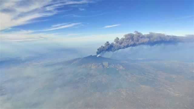 Jeden z najbardziej aktywnych wulkanów na świecie - Etna na Sycylii podczas wyrzucania kłębów dymu na początku lipca 2021 roku. Widok z samolotu (lot z Katanii do Katowic).
