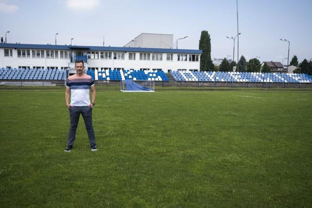 Prezes Stanisław Gajlewicz na tle trybuny stadionu i budynku klubowego.
