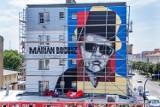 Pleszew. Mural  Mariana Bogusza w charakterystycznych dla siebie okularach słonecznych oraz w cylindrze już w całej okazałości