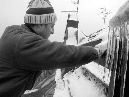 Marek Imiolek zrzuca niebezpieczne sople z budynku przy ul. Bożogrobców. Fot: MAGDALENA CHAŁUPKA