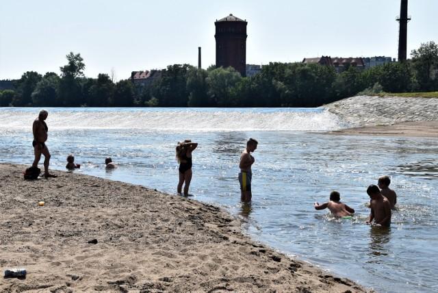 Upał w Brzegu. Ludzie wypoczywają nad Odrą, część szuka ochłody w rzece.