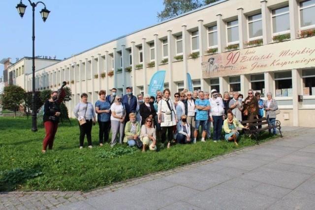 Początek spacer śladami Zygmunta Wilkońskiego. Jego uczestnicy pozują do fotografii przed gmachem inowrocławskiej biblioteki