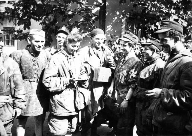 Grupa powstańców ze Starówki odpoczywa po ewakuacji kanałami na jednej z posesji przy ul. Wareckiej. Śródmieście Północne. 1 września 1944 r.
