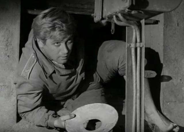 """Janek wkrada się do maszynowni mostu zwodzonego w Sztutowie, w odc. XVI pt. """"Daleki patrol""""."""