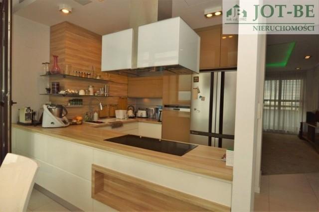 Nieruchomość posiada bardzo dobry układ z podziałem na część dzienną z salonem, kuchnią i wyjściem na taras, oraz część prywatną z trzema sypialniami, garderobą oraz łazienką.  Powierzchnia 133,5 mkw. obejmuje: - pokój dzienny (30,58 mkw.),  - trzy sypialnie (15, 15 oraz 26 mkw.), - dwie łazienki (5 i 6 mkw.), - kuchnię (24 mkw.),  - garderobę oraz przedpokój.  Do mieszkania przynależą także: - przepięknie oświetlony i zagospodarowany taras o pow. 26,83 mkw.,  - balkon o pow. 28 mkw.,  - ogród zimowy o powierzchni 15 mkw. Mieszkanie jest kompletnie wyposażone i umeblowane. Każdy z pokoi posiada pojemne szafy.  Zobacz na kolejnych slajdach najdroższe mieszkania we Wrocławiu - posługuj się myszką, klawiszami strzałek na klawiaturze lub gestami