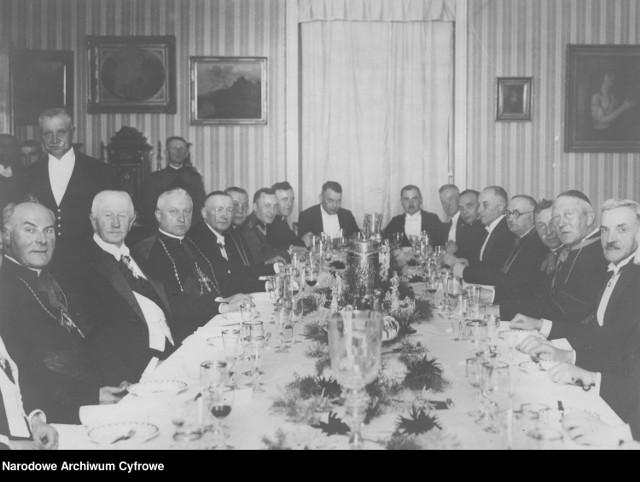 Uczestnicy przyjęcia przy stole. Od lewej widoczni m.in.: ks. kard. Michael von Faulhaber (1), hr. Bogdan Hutten-Czapski (2), ks. kard. prymas August Hlond (3), ks. ksiądz infułat Józef Kłos (5). Od prawej widoczni m.in.: sufragan gnieźnieński ks. biskup Antoni Laubitz (2), ks. prałat Tadeusz Zakrzewski (4), sekretarz i kapelan ks. kard. Hlonda ks. prałat Nikodem Mędlewski (6).