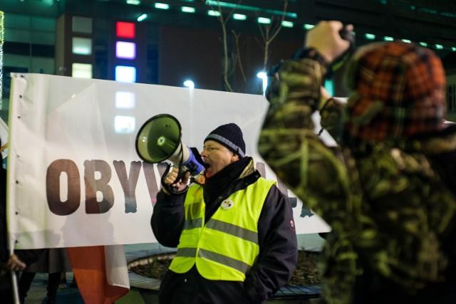 """W tym samym czasie, gdy w polskim parlamencie trwa ogromny chaos, przed Sejmem odbywa się protest KOD-u, który wspiera opozycję domagająca się odstąpienia przez partie rządzącą od projektów ustawy ograniczającej swobodę pracy dziennikarzy w Sejmie. Apelowano do marszałka Sejmu i Jarosława Kaczyńskiego, by zrezygnowano z tego pomysłu.  Informacja o proteście Komitetu Obrony Demokracji w bardzo szybkim tempie obiegła całą Polskę. Sympatycy KOD-u w największych miastach postanowili zaprotestować przeciwko propozycjom PiS.  Pikieta odbywała się także w Bydgoszczy. Przedstawiciele komitetu zebrali się przy ulicy Gdańskiej, gdzie mieści się siedziba bydgoskiego klubu PiS. Na miejscu było kilkadziesiąt osób.   """"Precz z Kaczorem, dyktatorem!"""" - skandowali uczestnicy protestu.  Przed godziną 22 manifestacja odbywała się w milczeniu, by nie zakłócać ciszy nocnej."""