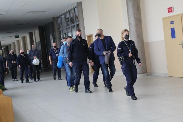 Oskarżeni idą w konwoju policji na proces przed krakowskim sądem